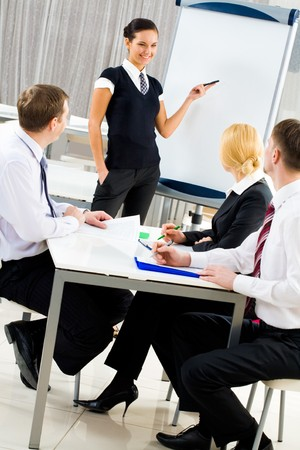 Smart and confident employee pointing at whiteboard while presenting her ideas Stock Photo - 4549485