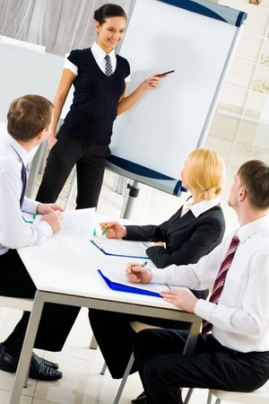 image consultant: Image of several listeners looking attentively at young consultant pointing at board