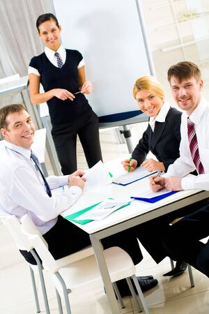 Portrait of executive business group sitting at table and smiling at camera with smart teacher on background Stock Photo - 4544948