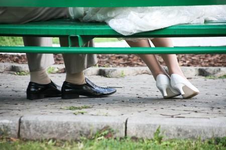 banc de parc: Close-up des jambes de jeunes mari�s en vertu de banc dans le parc en mariage