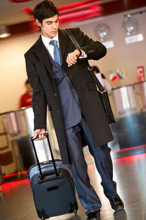 airport business: Photo of busy young man waiting for his plane in the airport
