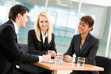 Portrait of friendly business team sitting around table and communicating in office Stock Photo - 4549480
