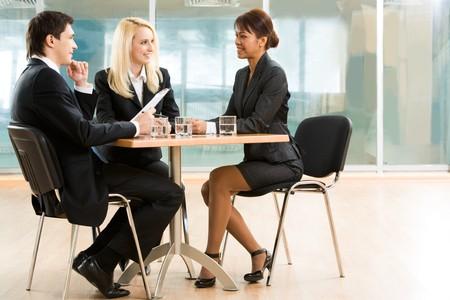 entrevista: Tres socios de negocios discutir asuntos importantes en reuni�n de trabajo Foto de archivo