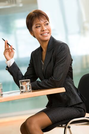 Portrait of African businesswoman sitting at the table during conference and looking aside Stock Photo - 4549435