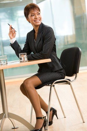 Happy business leader sitting at workplace with pen in hand in the office Stock Photo - 4549524