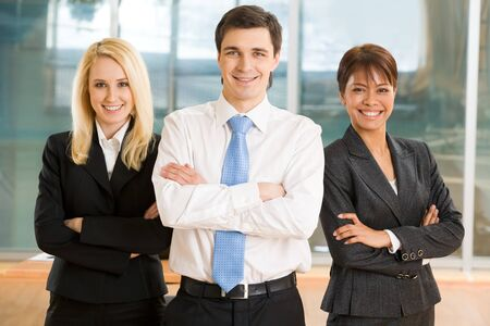 spokesperson: Image of cheerful colleagues keeping their arms crossed and looking at camera with smiles Stock Photo