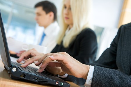 Close-up of human hands typing on laptop keyboard with working people at background photo