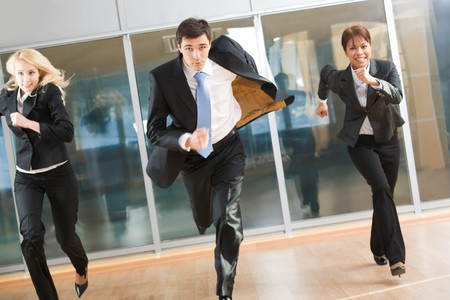 Portrait of hurrying people in suits running forwards for work with optimistic expression photo