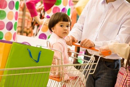 Portrait of small girl sitting in handcart while shopping with her parents photo