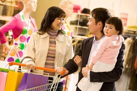 Portrait of friendly family shopping together with shop window at background photo