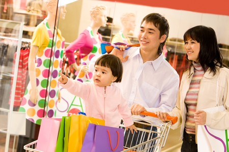 Image of cute toddler showing something to her parents in shop while they looking at it with smiles photo