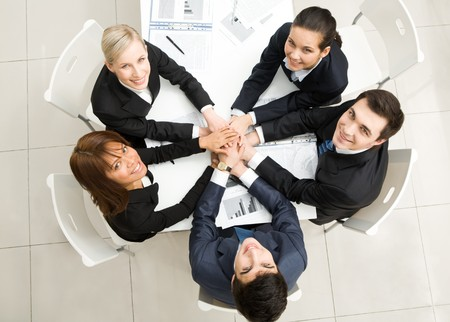 looking upwards: Image of business people with their hands on top of each other and looking upwards Stock Photo
