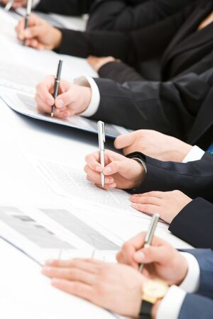 Image of row of people hands writing on papers at seminar Stock Photo - 4554761