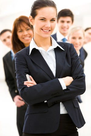 Portrait of successful businesswoman looking at camera on background of several employees Stock Photo