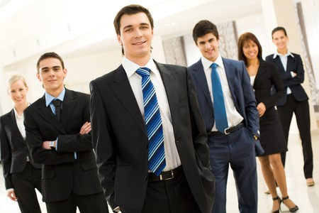 Smart businessman looking at camera at background of his friendly partners Stock Photo - 4544899