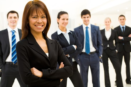 white achievement: Portrait of successful businesswoman looking at camera with her workteam at background