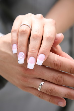 Close-up of bride�s hand on that of her husband after exchange of wedding rings photo