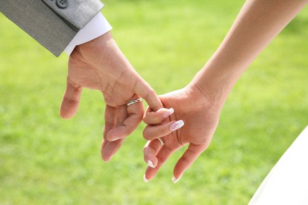 Close-up of bride�s hand holding that of her husband over green background