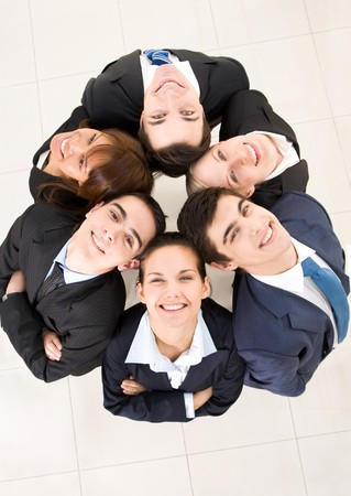 Above view of several business partners looking upwards at camera with their heads close to each other Stock Photo - 4544916