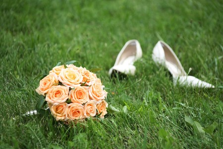 outdoor event: Close-up of bridal yellow rose bouquet on background of her white shoes on green grass Stock Photo