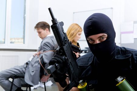 Photo of terrorist in balaclava holding gun on background of bound office workers photo