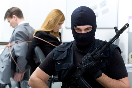 stealer: Portrait of man wearing black balaclava with gun looking at camera on background of scared business people