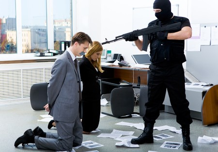 Image of two office workers standing on their knees in front of evil robber pointing gun at them Stock Photo