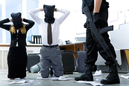 stealer: Photo of kneeling businesspeople wearing black sacks on their heads with burglar standing near by