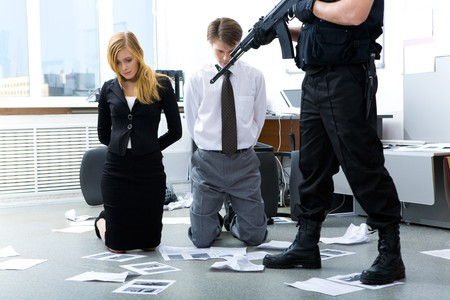 Legs of criminal with gun pointed at scared man and woman in office photo