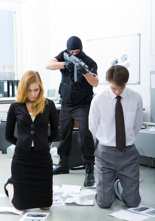 Photo of business co-workers standing on knees being aimed at by evil terrorist Stock Photo