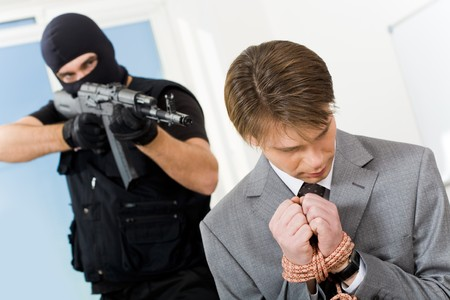 Portrait of confused businessman with bound hands being chased by gangster pointing gun at him Stock Photo - 4549297