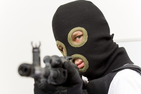 violence and trigger: Head of murderer in balaclava pointing his gun at camera and looking into it Stock Photo
