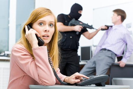 stealer: Portrait of horrified businesswoman pushing buttons of telephone while terrorist threatening her colleague at background