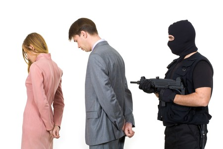 Portrait of two businesspeople standing with terrorist pointing gun at them behind