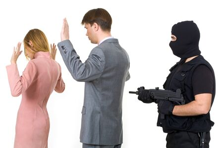 Two victims standing with their hands raised while mafia representative pointing gun at them behind Stock Photo - 4544891