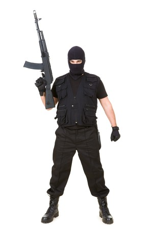 Portrait of dangerous bandit in black wearing balaclava and holding gun in hand photo