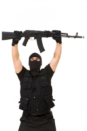Portrait of terrorist in balaclava holding rifle above himself on white background photo