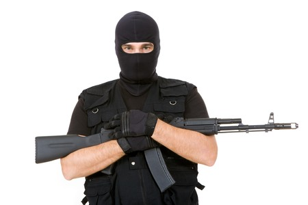 Portrait of violent killer holding firearm and looking at camera with balaclava on his head photo