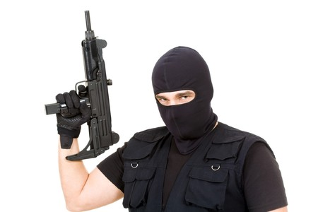 Portrait of confident terrorist with weapon in hand looking at camera on white background