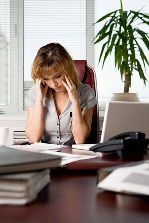 Image of thoughtful businesswoman touching her head while looking at document and reading it photo