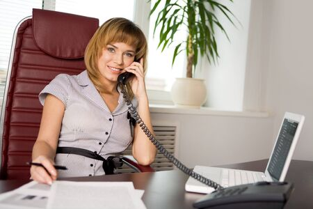 Portrait of female manager speaking on the phone and looking at camera with smile Stock Photo - 4549459
