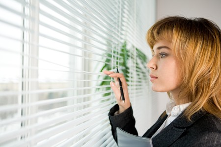 congenial: Profile of confident female looking outside through venetian blinds