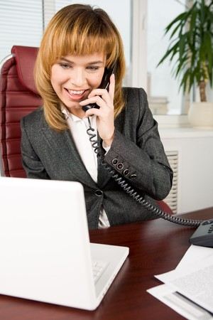 Image of successful female looking at laptop screen and talking on the phone photo