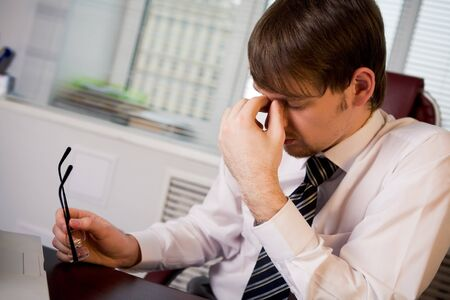 Photo of fatigue man with his eyeglasses off keeping his hand near face after hard working day Stock Photo - 4544886