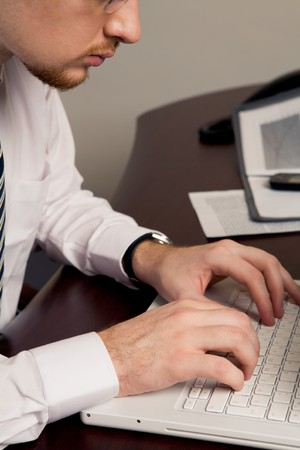 Image of busy man typing new business plan on laptop keypad photo