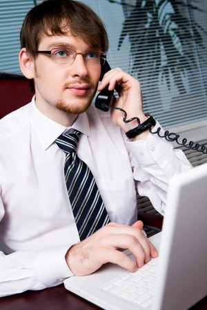 Portrait of handsome businessman speaking to his partner on the phone in office photo