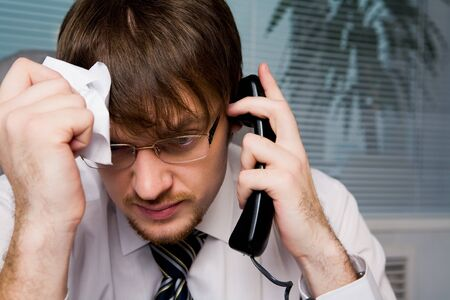 Portrait of frustrated employer calling on the phone and holding crumpled paper in hand Stock Photo - 4549447