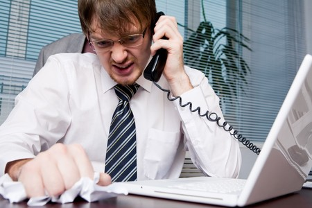 phoning: Nervous businessman crumpling document while speaking angrily to someone on the phone