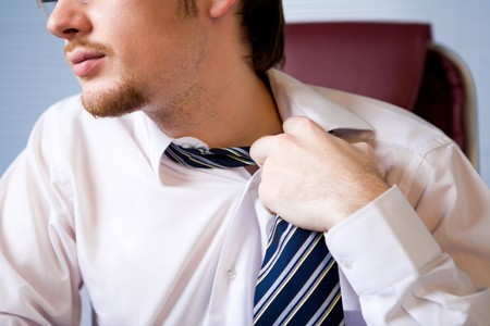 loosen: Close-up of annoyed businessman loosing his tie to relax a bit after hard work Stock Photo