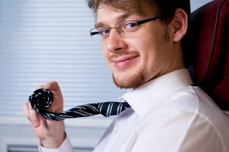 Smart ceo looking at camera with smile and holding his rolled tie photo